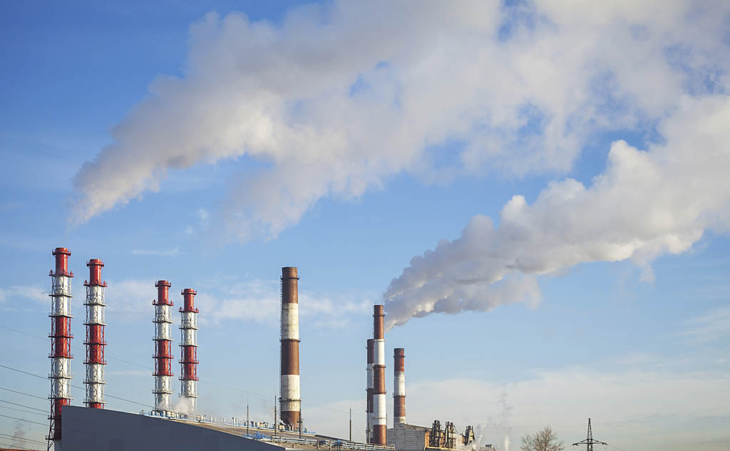 Industrial landscape. Power plant tubes with smoke above blue sk